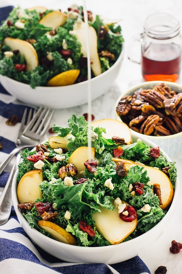 Pear gorgonzola caramelised pecans salad with dressing being poured on.