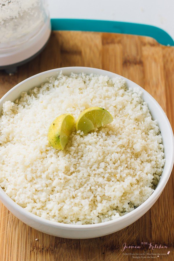 A bowl of cauliflower rice, topped with lemon wedges.