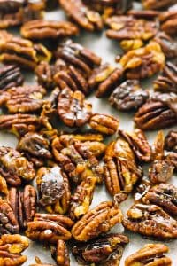 Top down shot of candied pecans on a baking tray.