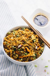 Quinoa fried rice in a white bowl with chopsticks on the side.