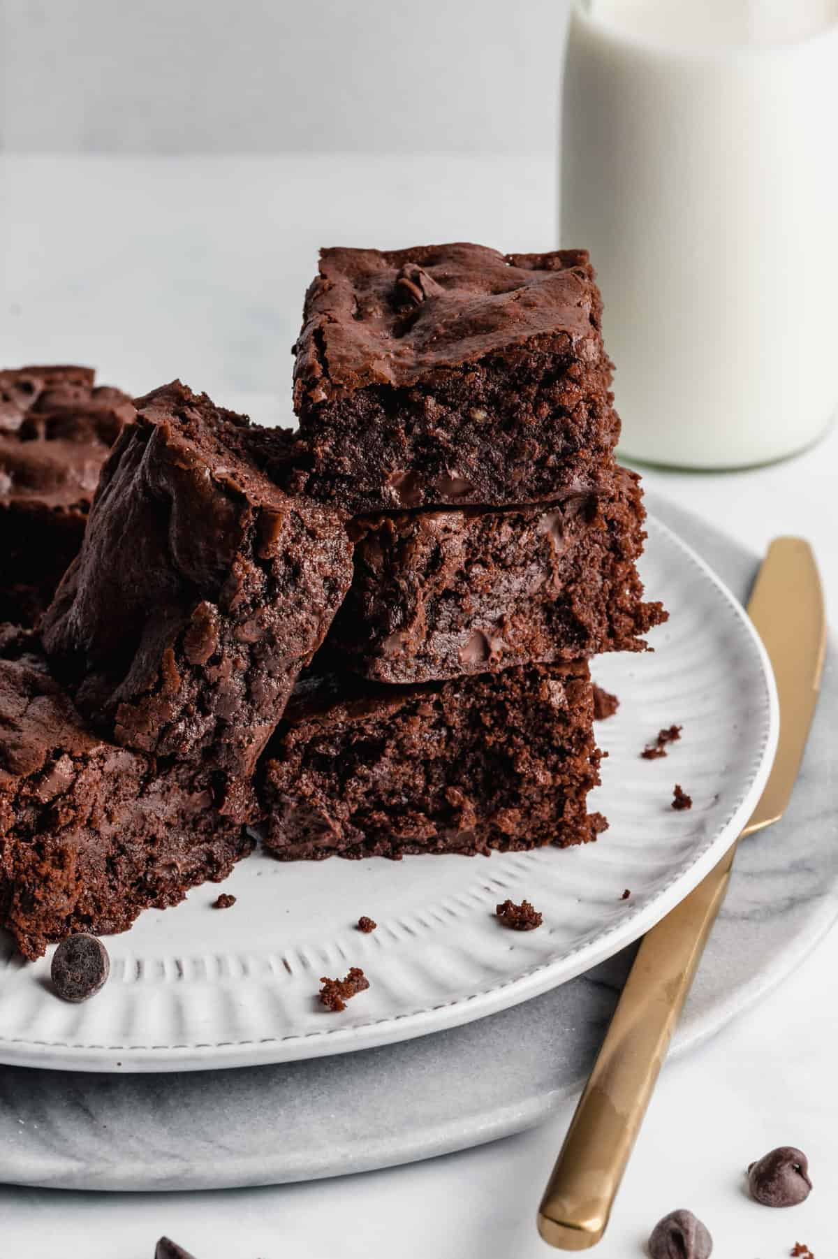 Brownies stacked on a plate with knife beside it.