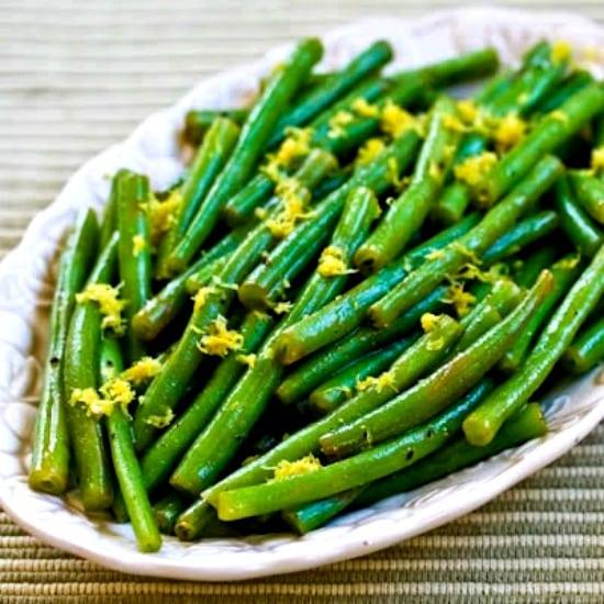 Lemony green beans on a long white dish.