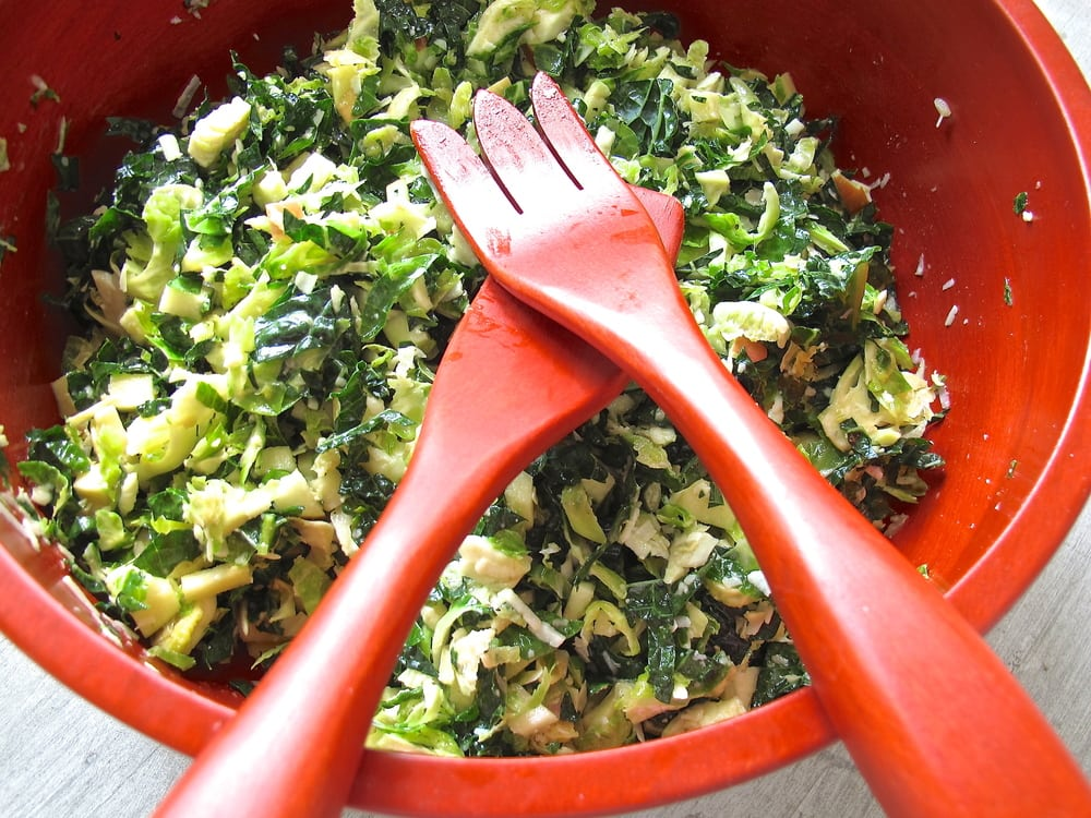 Kale and brussels sprout salad in a red bowl.