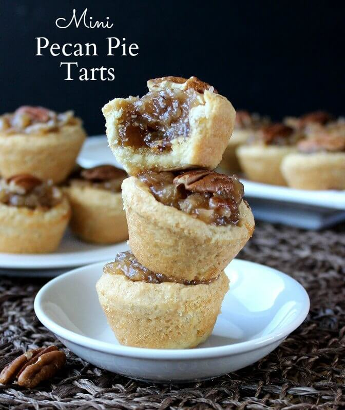 A stack of mini pecan pie tarts on a white dish.