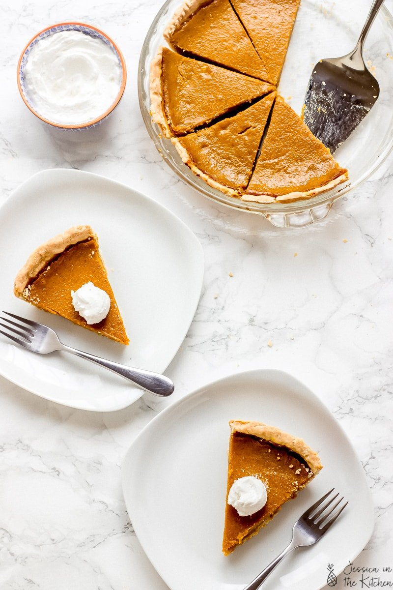 Overhead shot of pumpkin pie slices on plates and a baking dish.