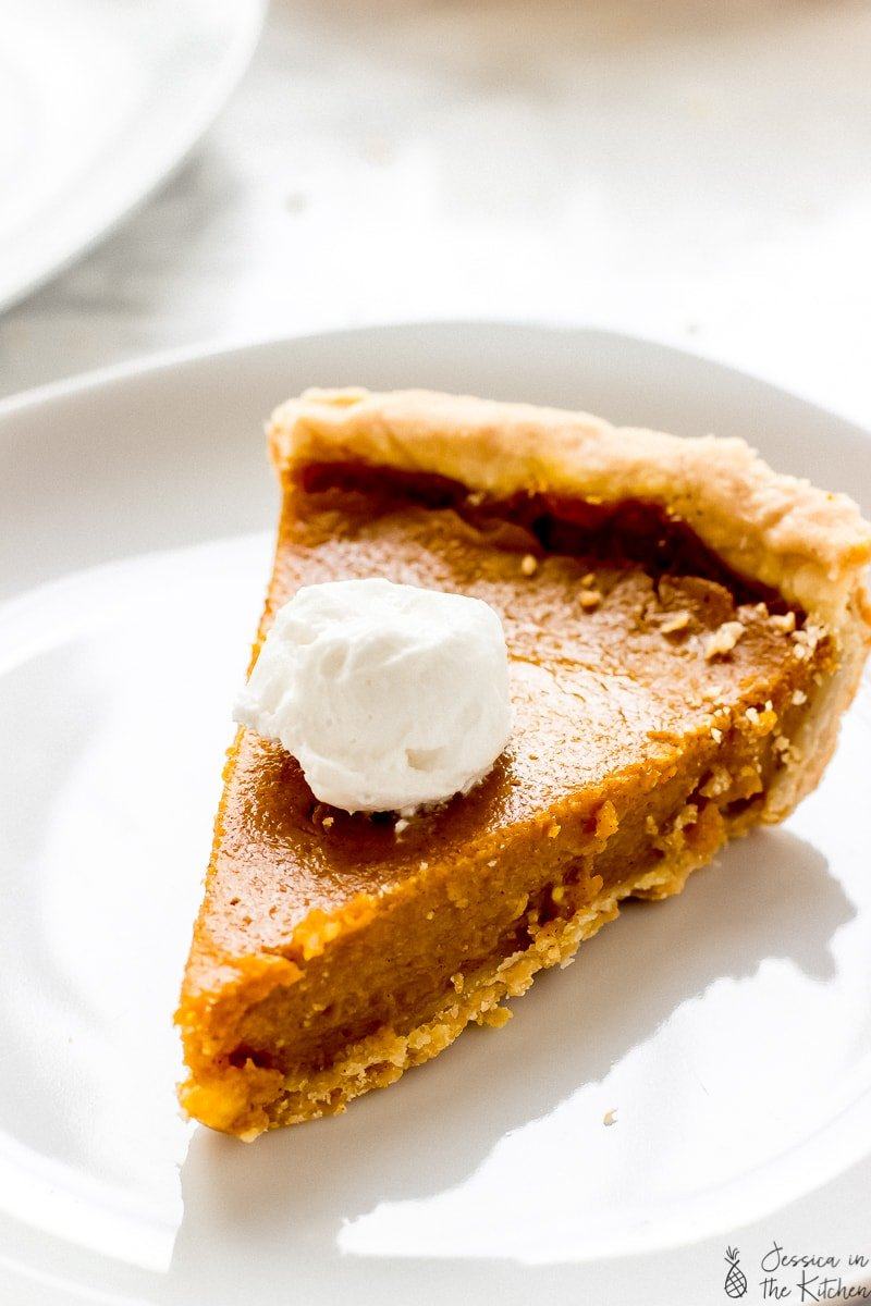 A slice of pumpkin pie with cream on top.