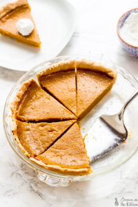 Top down shot of sliced pumpkin pie in a glass dish.