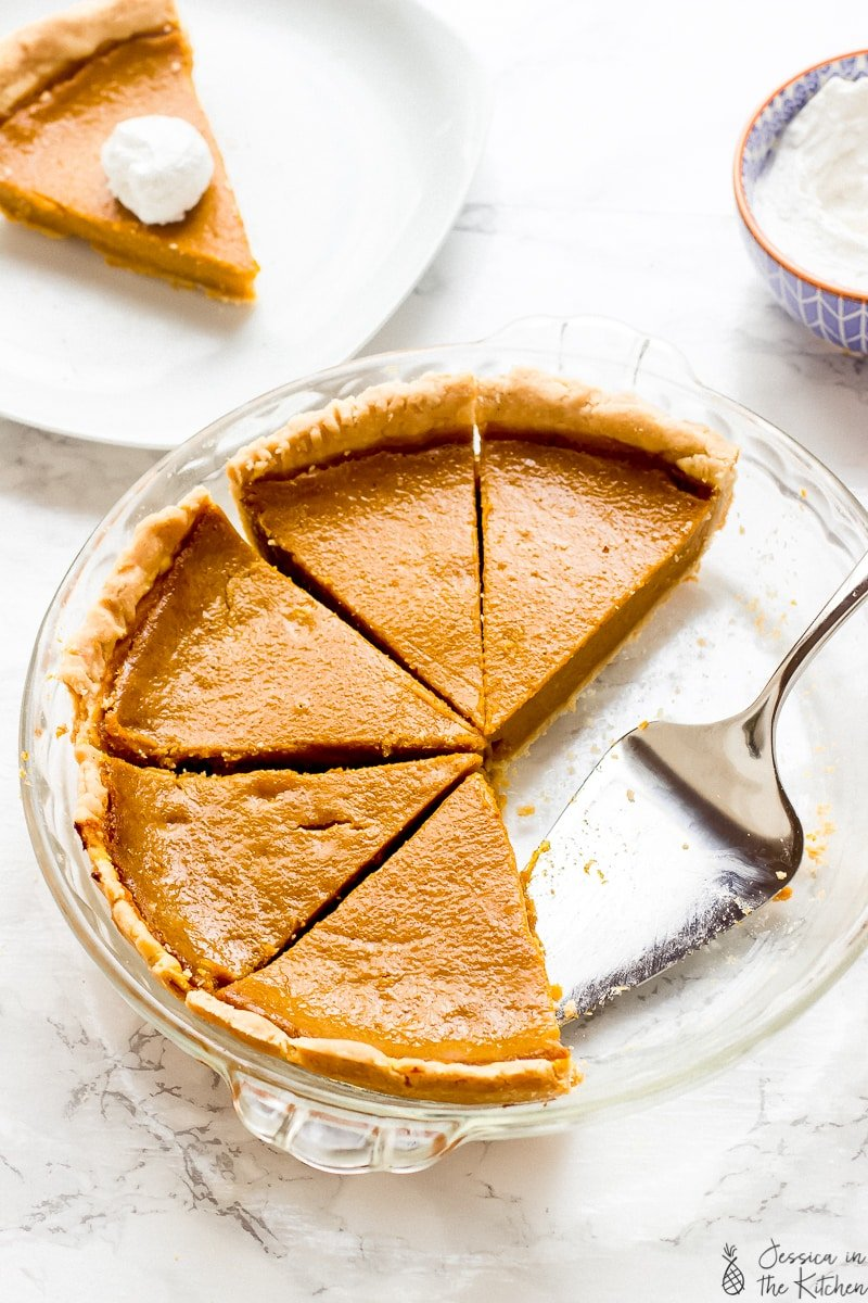 pumpkin pie sliced up in a pie dish with a slice also on a plate behind it