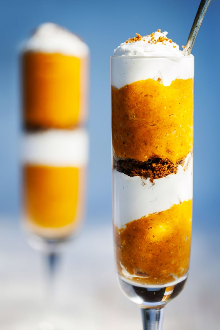 Two tall glasses of pumpkin pie parfait in front of a blue background.