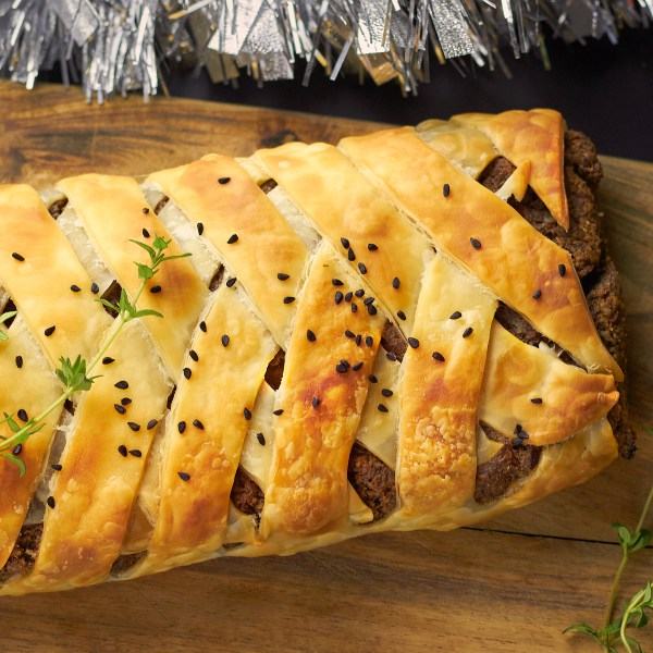Top down shot of pecan and mushroom wellington on a wooden chopping board.
