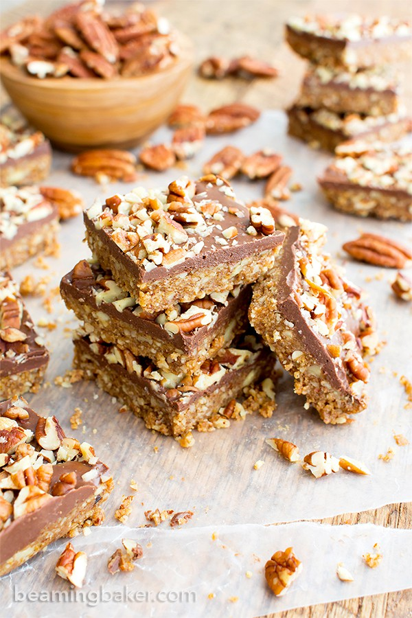 A stack of paleo pecan bars surrounded by pecans.
