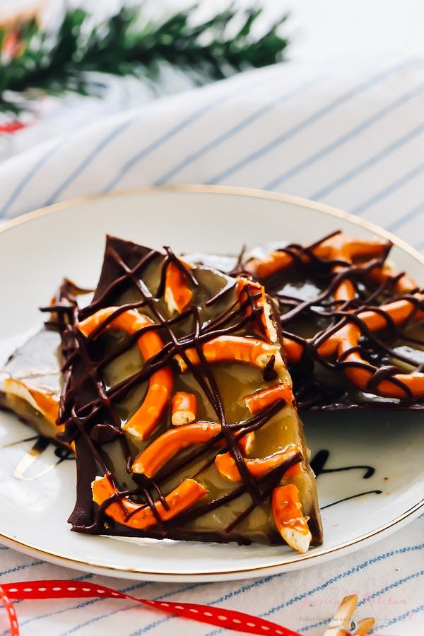Chunks of slated caramel pretzel chocolate bark on a white plate.