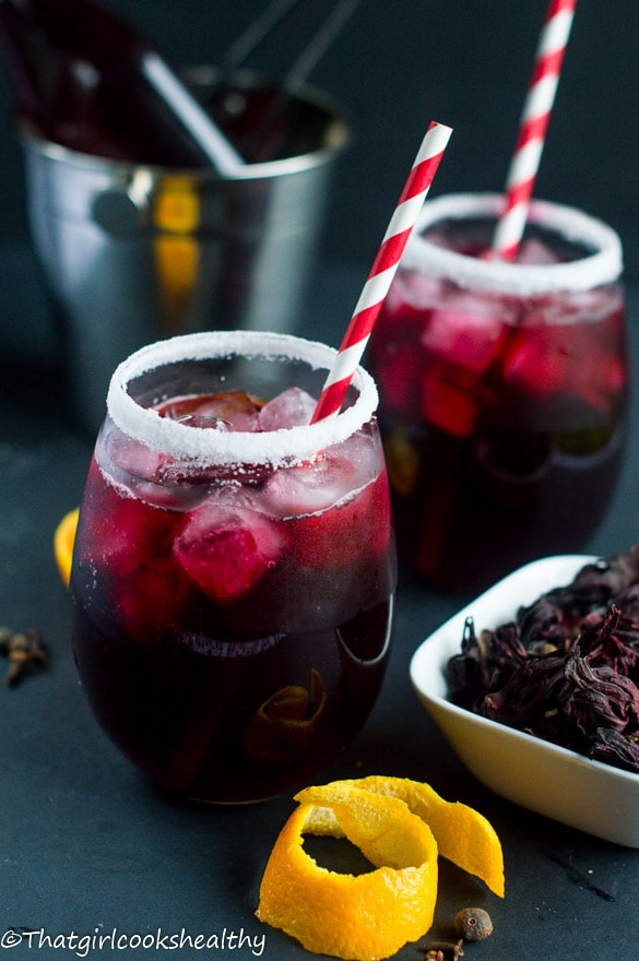 Two glasses of sorrel drink with red straws.