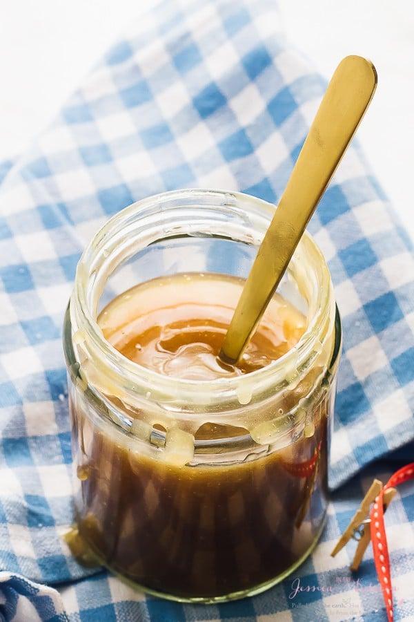 gold spoon in jar of vegan caramel sauce