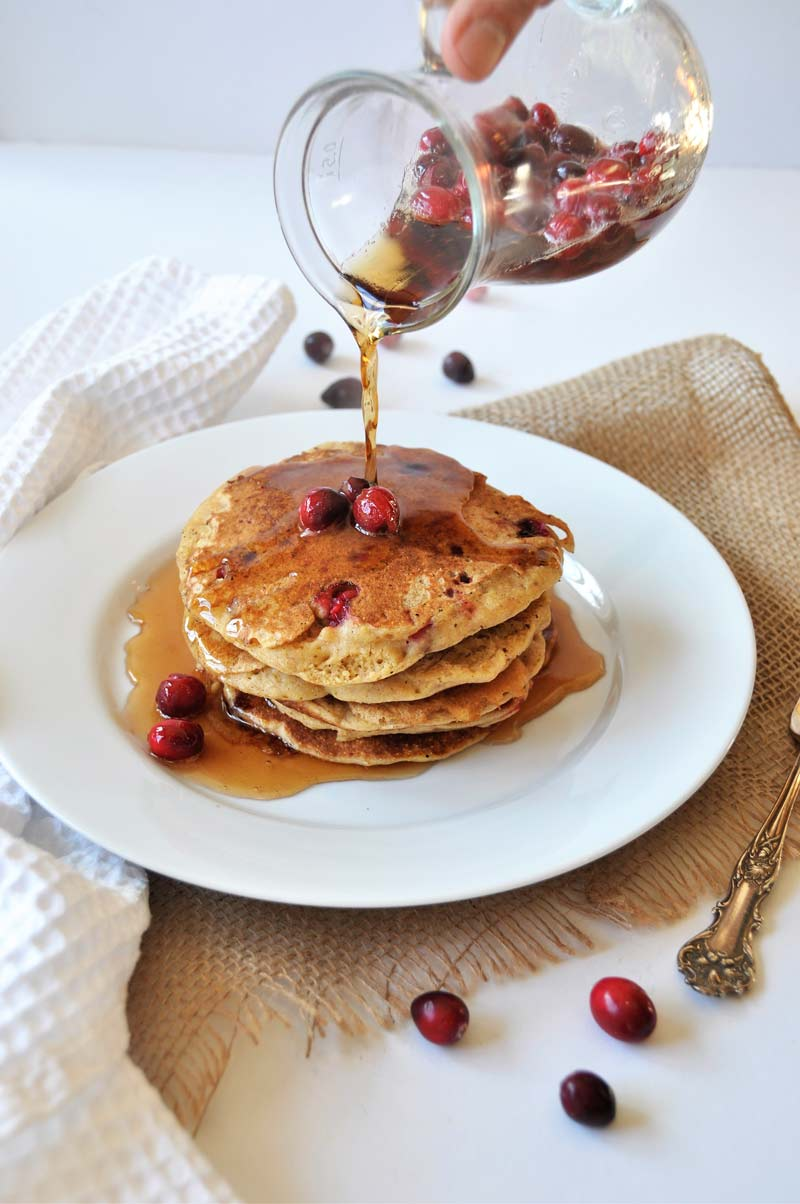 Pouring syrup on a stack of orange cranberry pancakes.