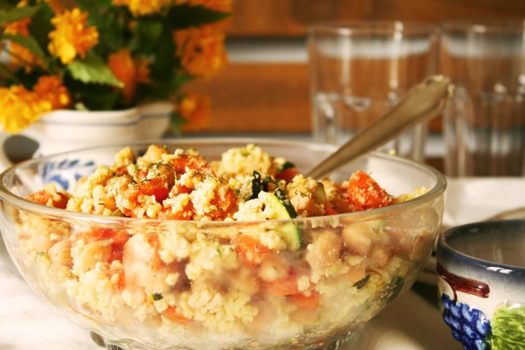 Side shot of a glass bowl of millet salad.