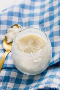 Overhead shot of coconut butter in a glass with a golden spoon on the side.