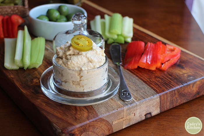 Jalapeno cashew spread in a glass jar on a charcuterie board with raw vegetables.