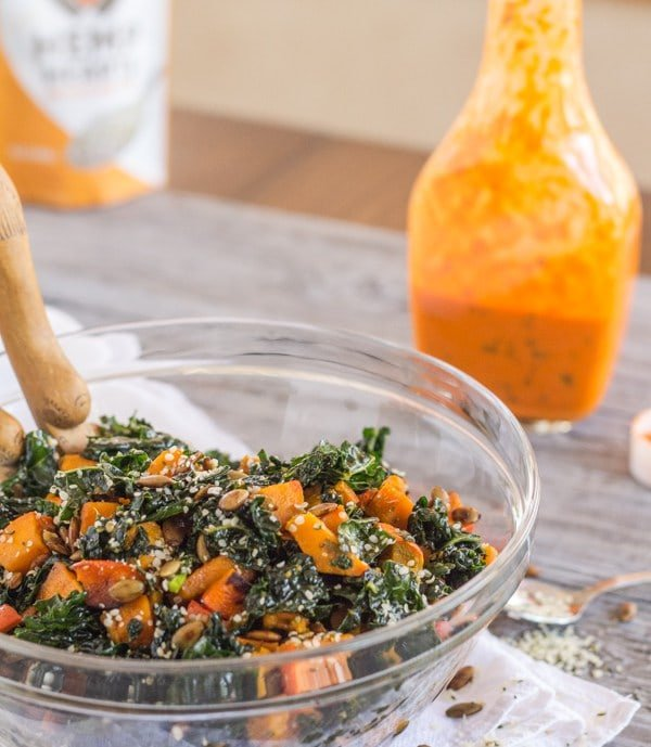 Kale and squash salad in a glass bowl with dressing in the background.