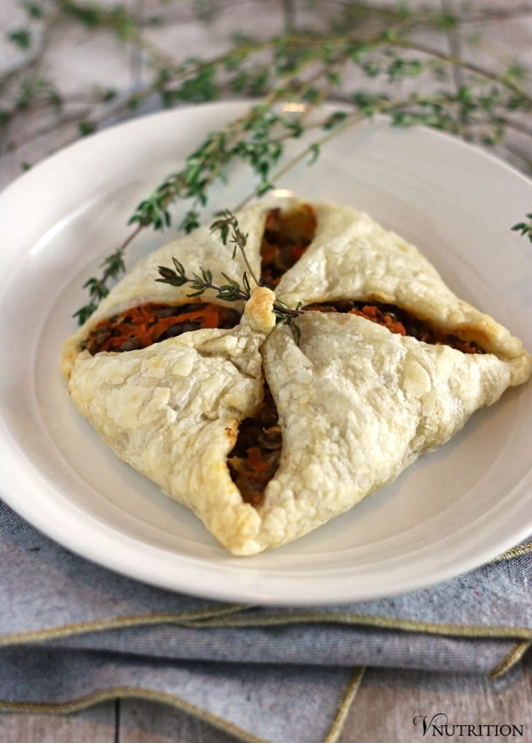 A lentil puff pastry pocket on a white plate with herb garnish.