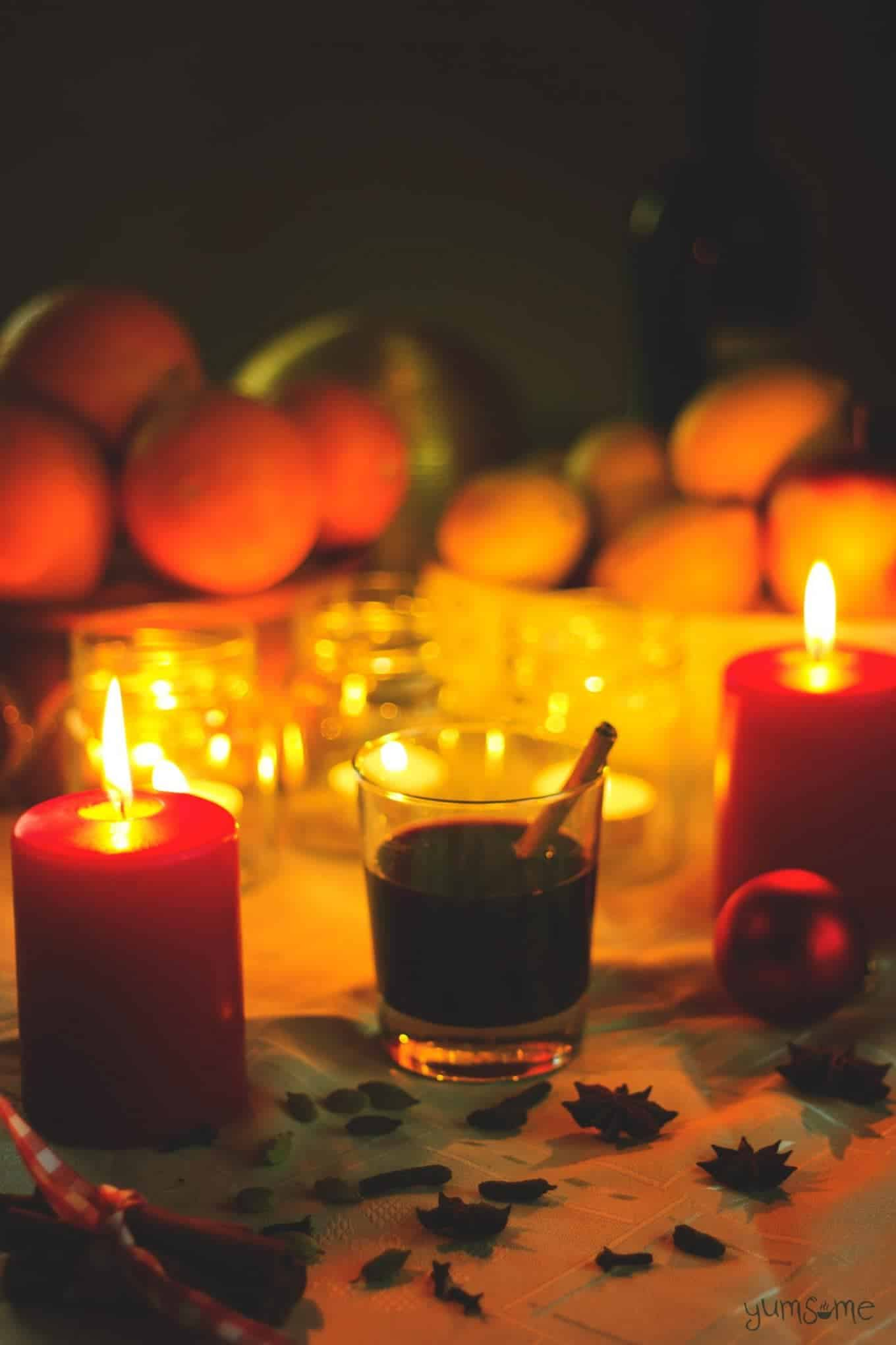 A glass of mulled wine surrounded by candles.