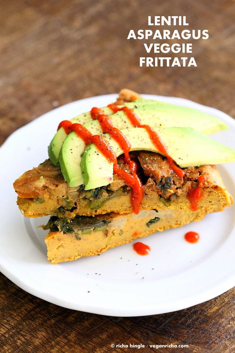 Two slices of veggie frittata topped with slices of avocado.
