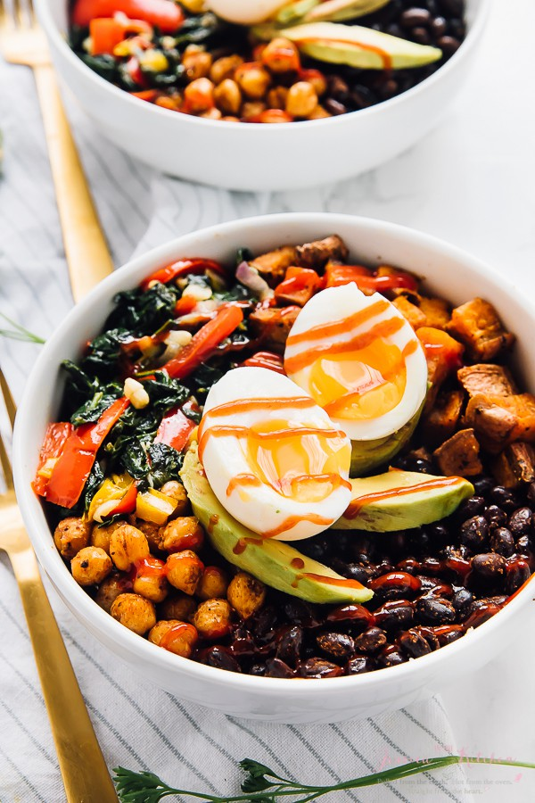 Protein breakfast bowl on a striped cloth with a golden fork on the side.