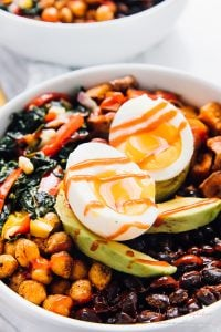 A close up of a breakfast bowl with sliced avocado and sliced egg on top.