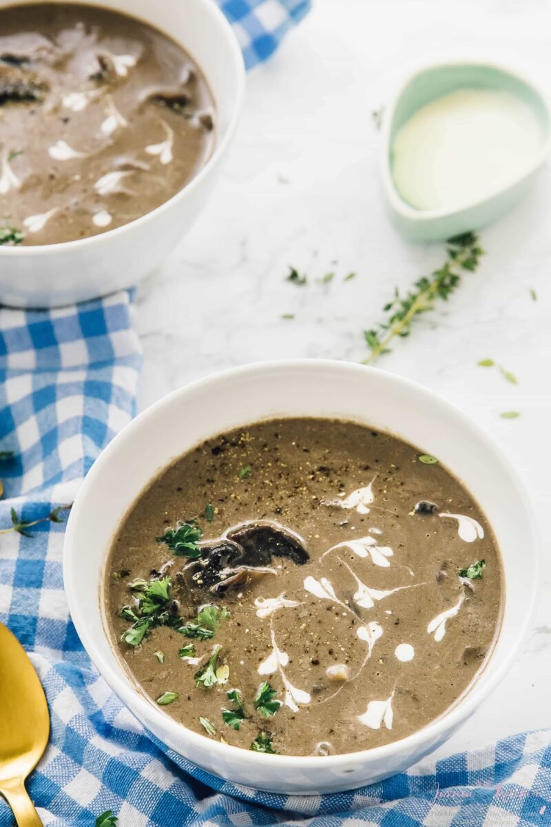 A bowl of creamy mushroom soup with rosemary garnish and a gold spoon on the side.