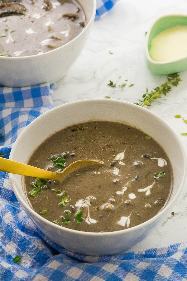 A golden spoon dipping into a white bowl of creamy mushroom soup.