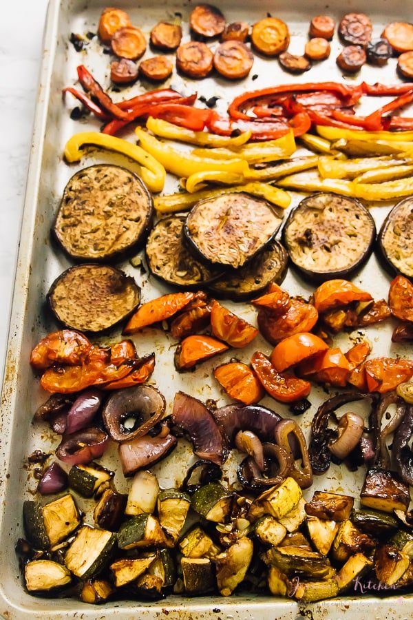 Roasted vegetables on a silver baking tray.