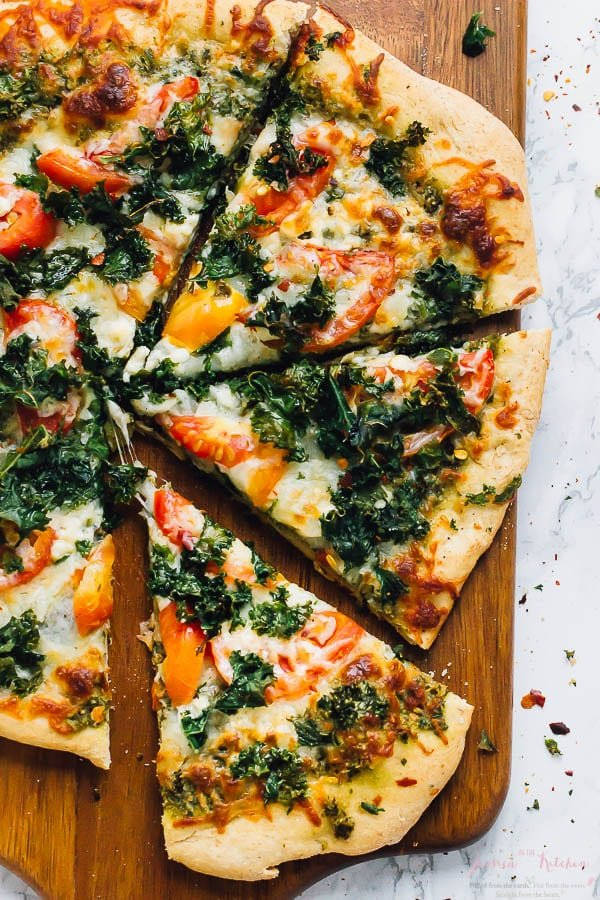 Top down shot of kale pesto pizza slices on a board.