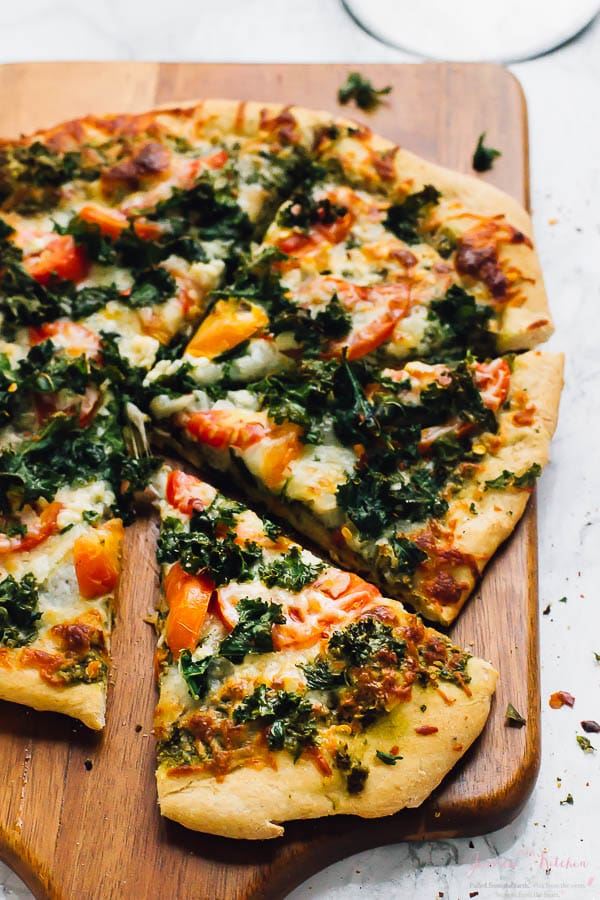 Slices of kale and pesto pizza on a wooden board.