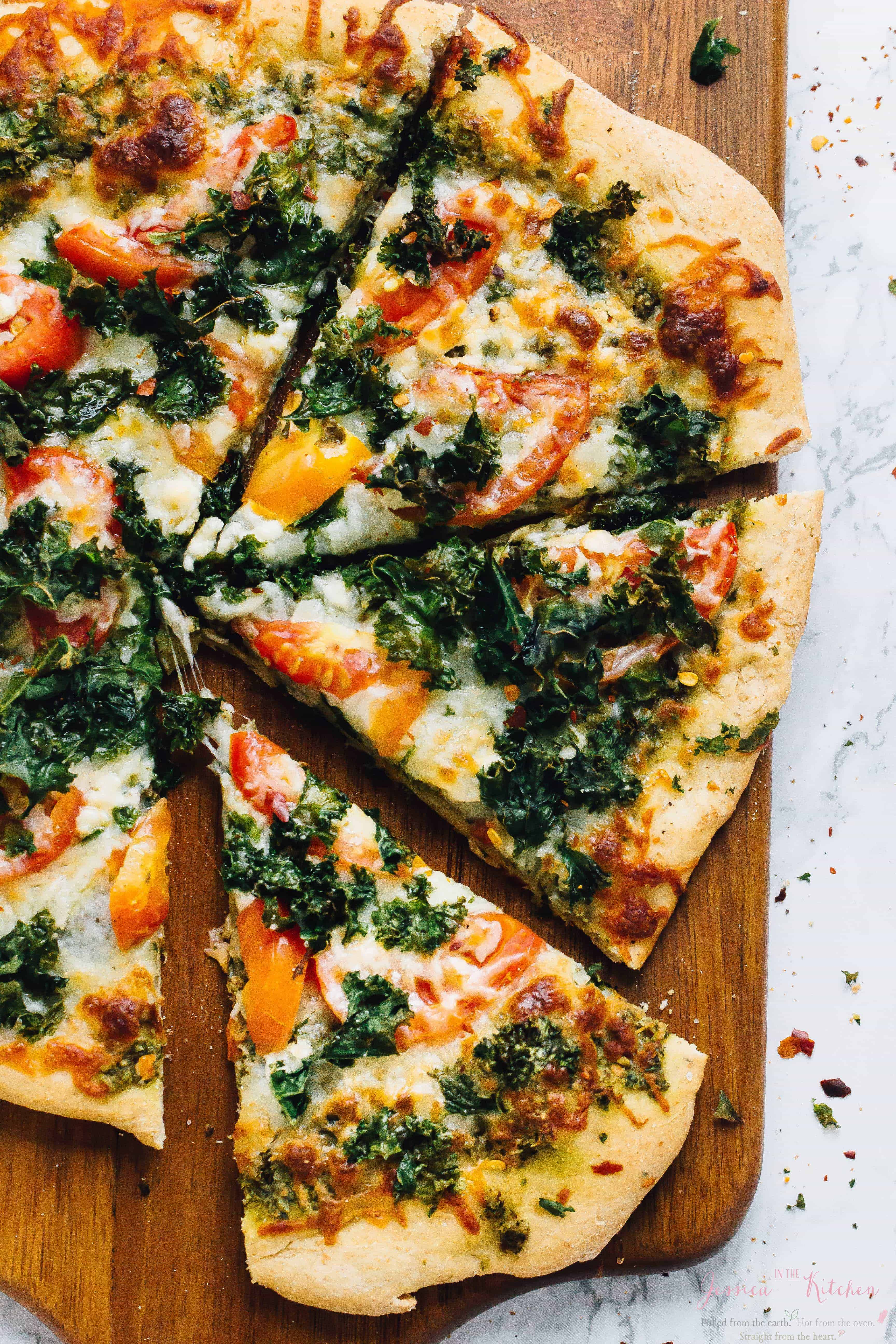 Sliced kale pesto pizza on a wooden board.