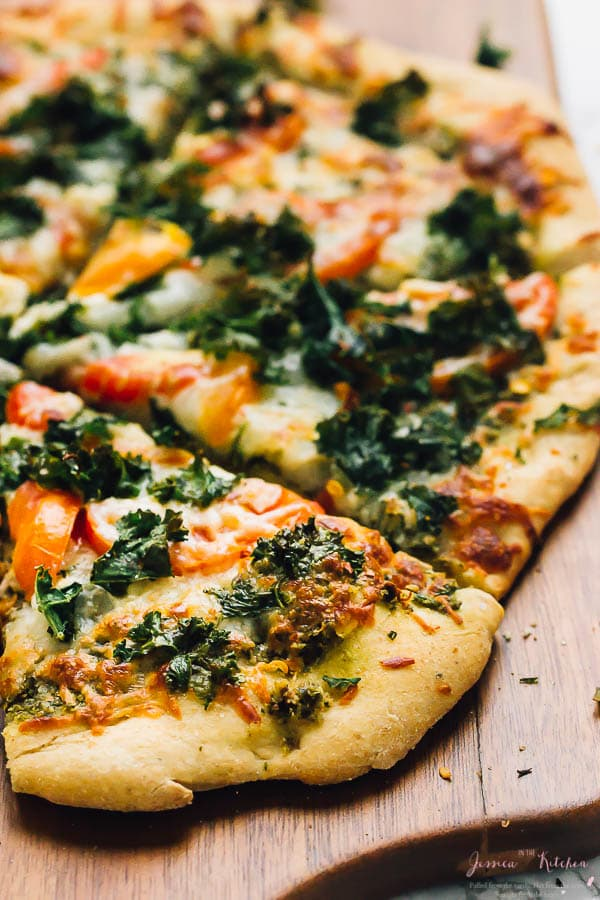 Close up of a kale pesto pizza on a wood board.