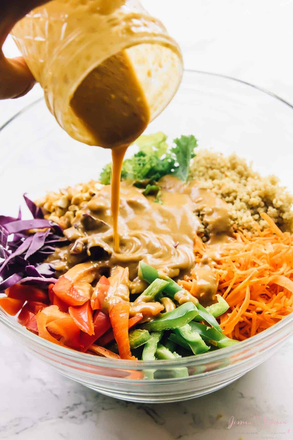 The peanut ginger sauce sauce being poured into a clear glass bowl with salad fixings in them