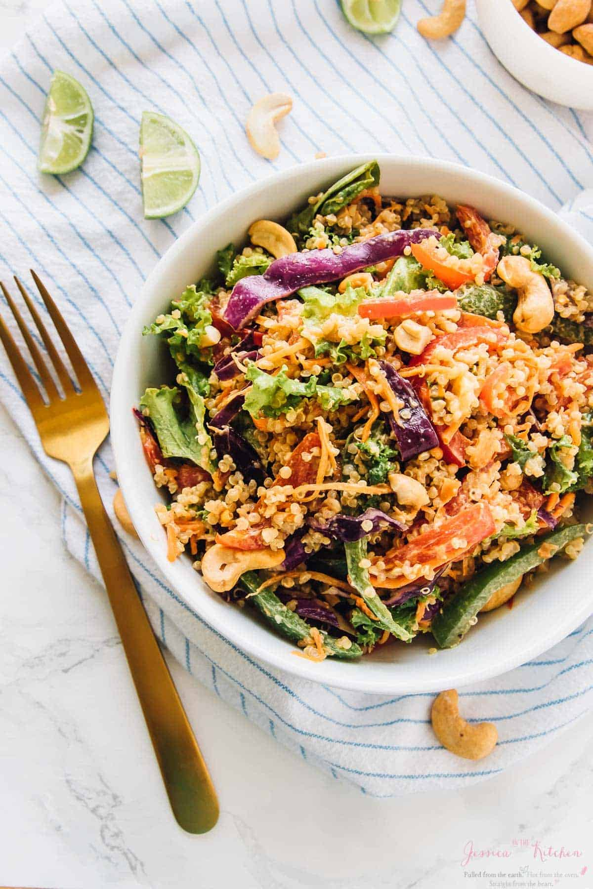 Cashew thai quinoa salad in a white bowl with a gold spoon and lime wedges on the side.