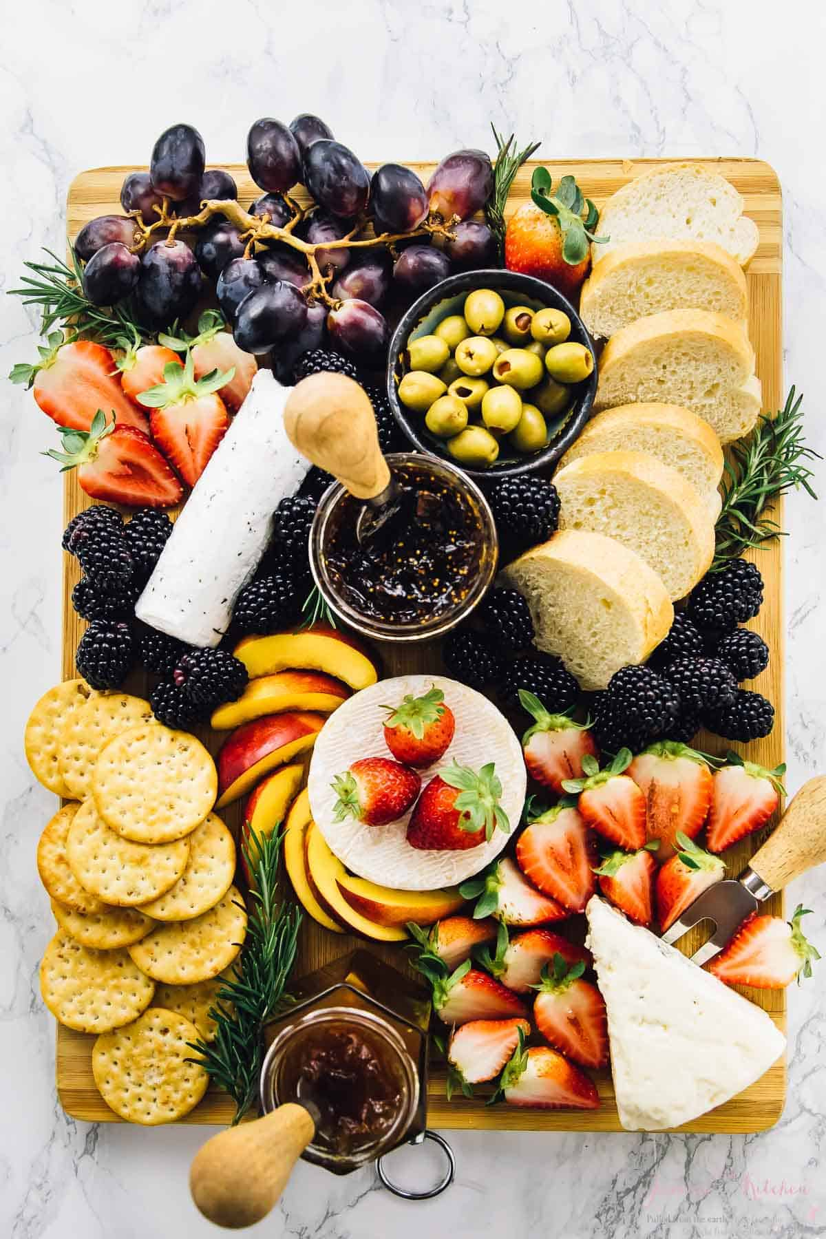 Top down shot of cheeseboard with fruit and bread.