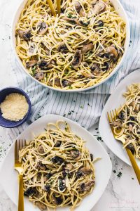 Garlic mushroom pasta on two plates and in a skillet.