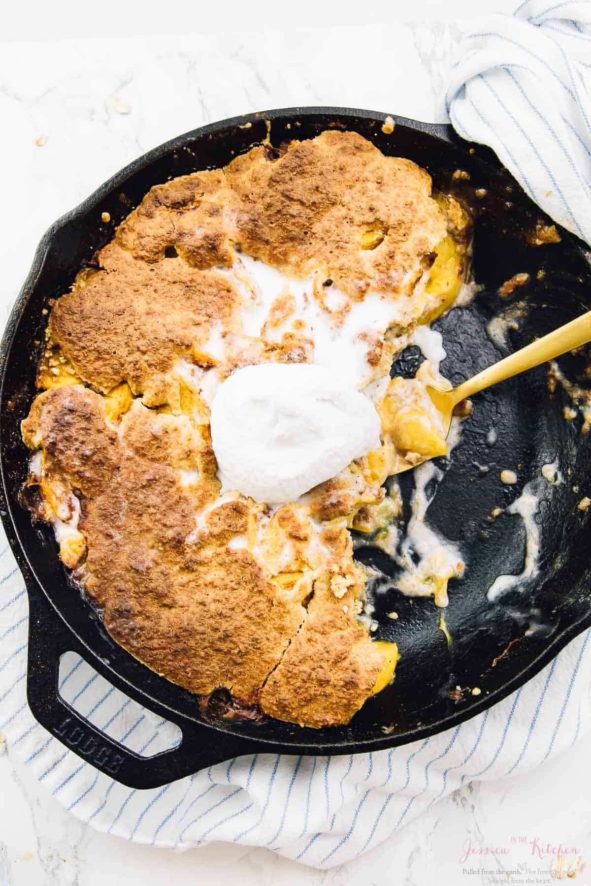 Top down shot of peach cobbler in a skillet with cream on top.