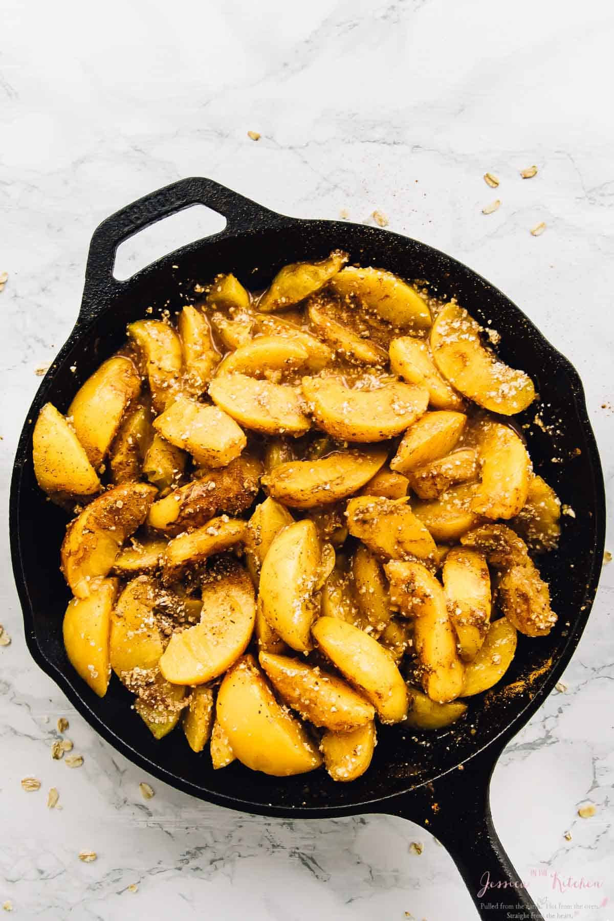 Peach slices cooking in a black skillet.