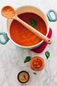 Roasted garlic tomato sauce ina big pot with a spoon on top.