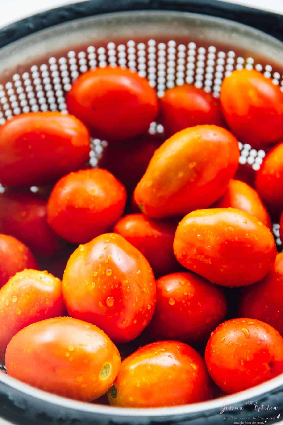 Close up of cherry tomatoes in a colander.