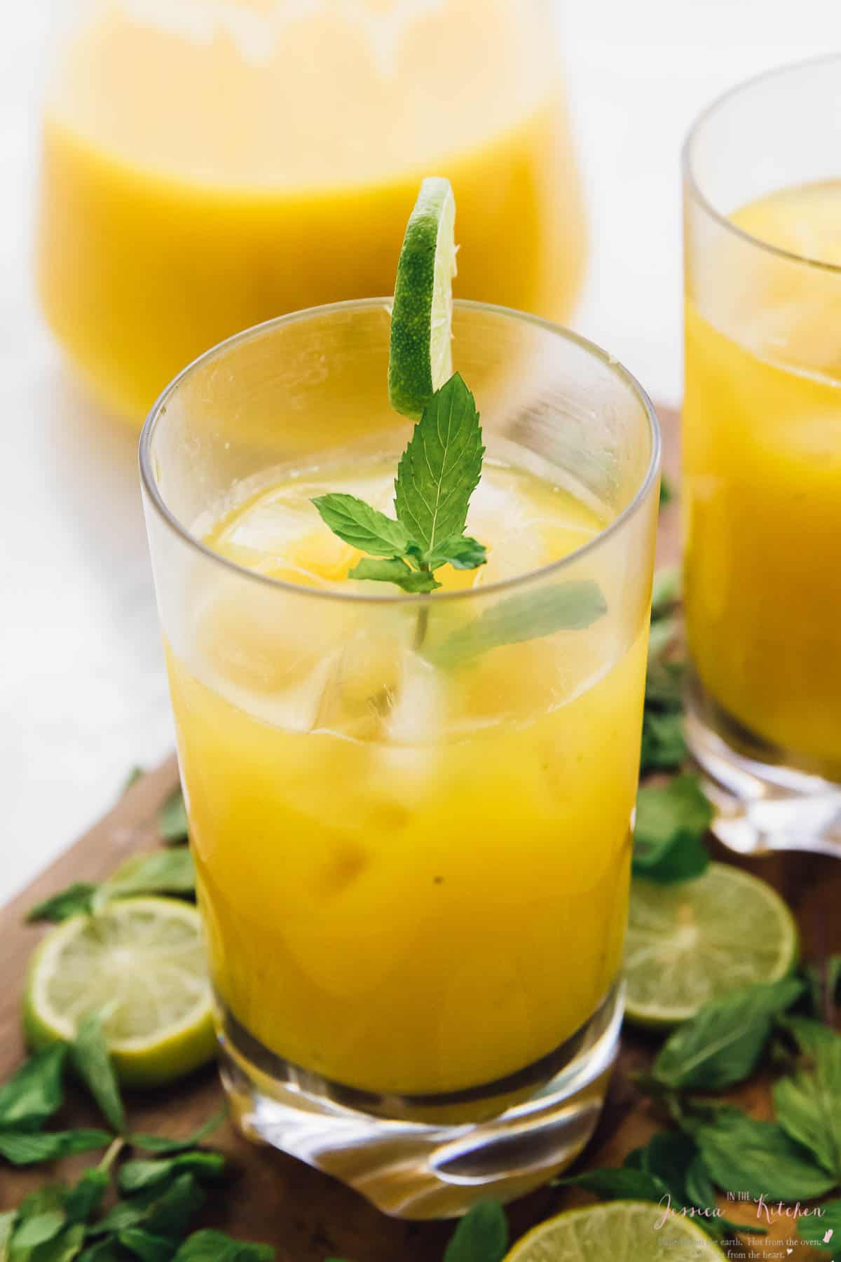 A mango mojito in a glass, garnished with mint and lime.
