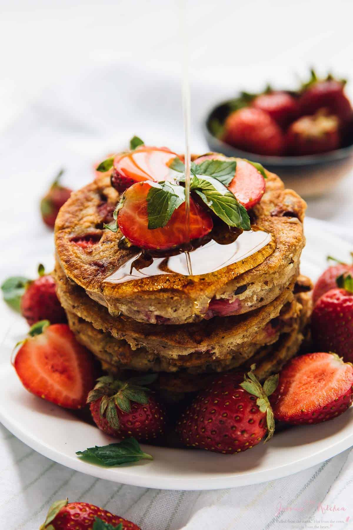 A pile of fluffy vegan strawberry pancakes drizzled with syrup.