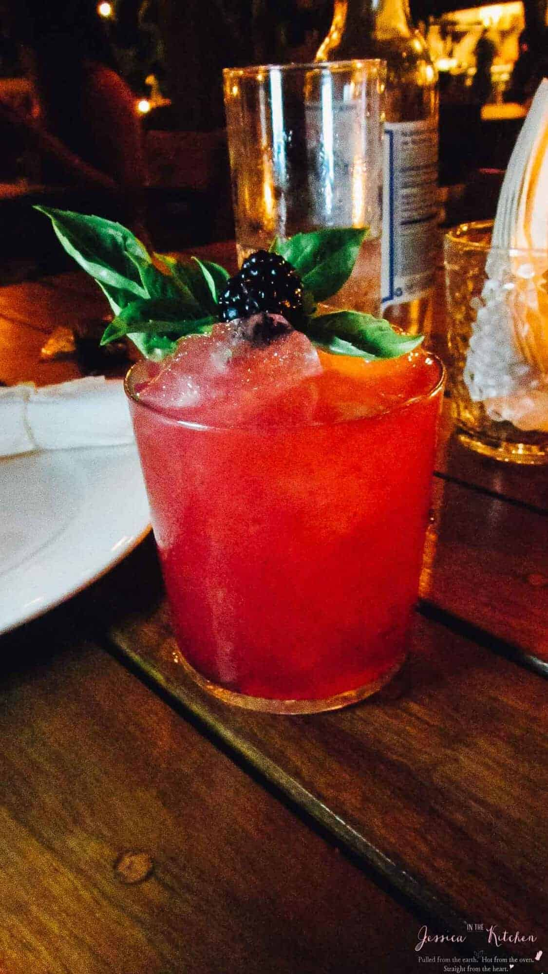 A red cocktail with blackberry garnish, on a wood table.