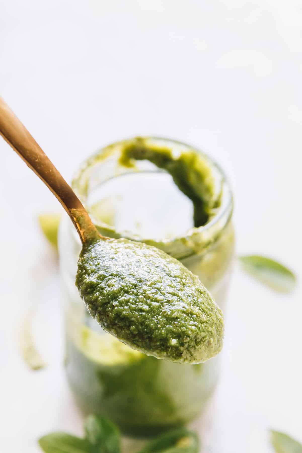 A gold spoon with basil pesto.