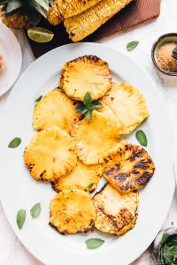 Overhead view of grilled pineapple slices with mint garnish.