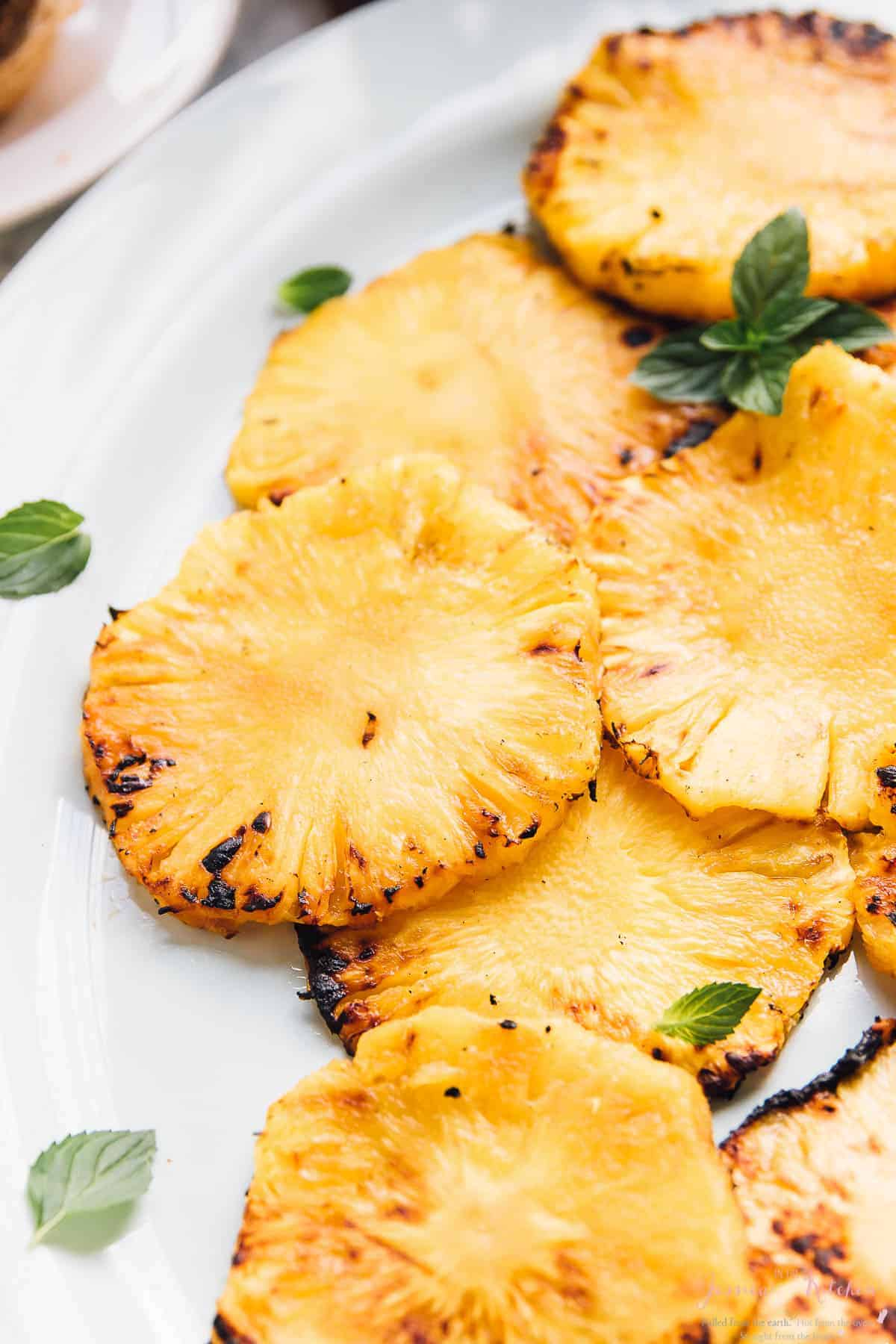 Slices of grilled pineapples on a white dish.