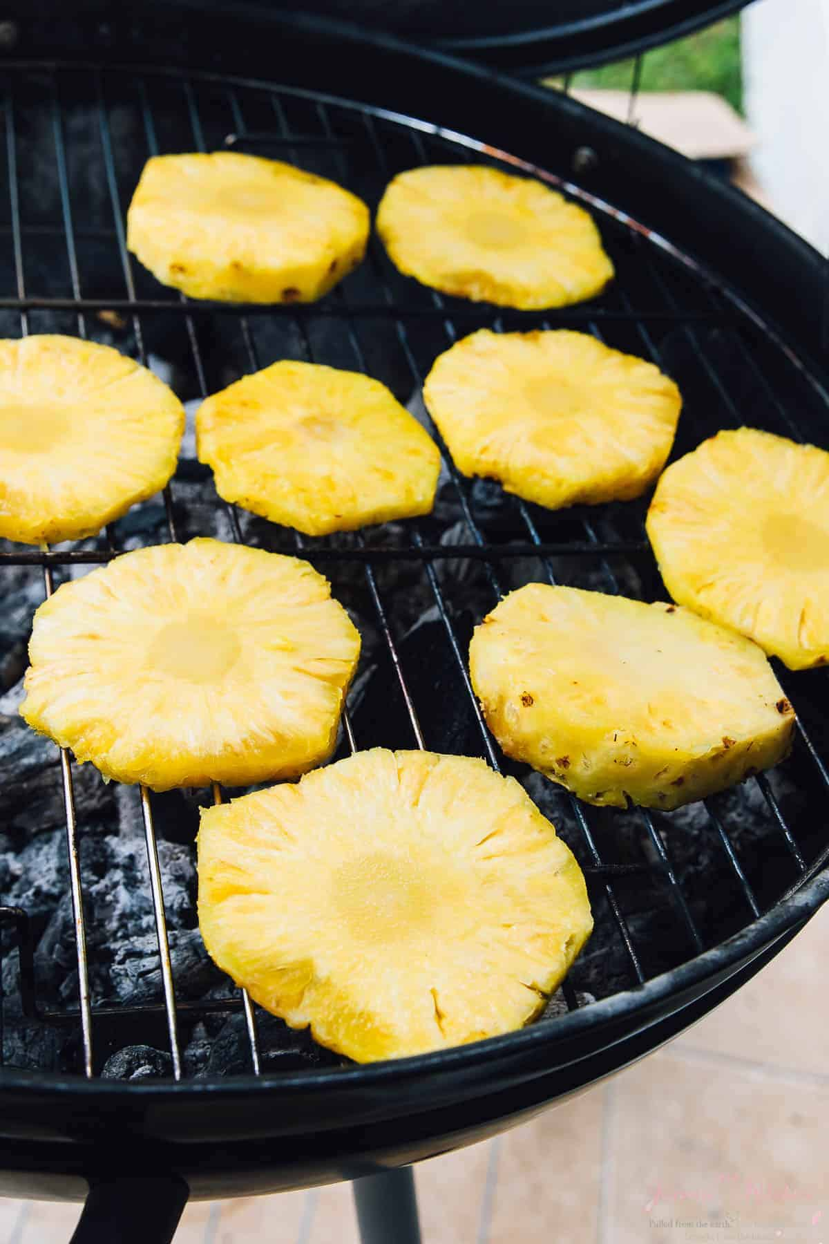Slices of pineapple on a BBQ grill.